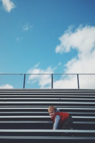 Climbing the bleachers of his sister's track meet.