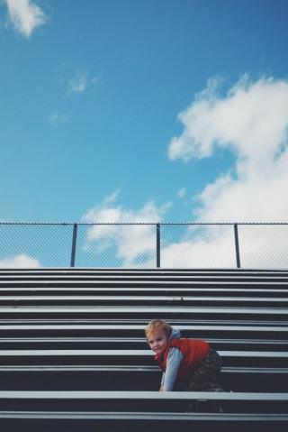 Climbing the bleachers of his sister's track meet.