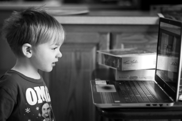 Watching the daily video for his brother's schooling. He loves it and is, I believe, learning more than his bro is these days...